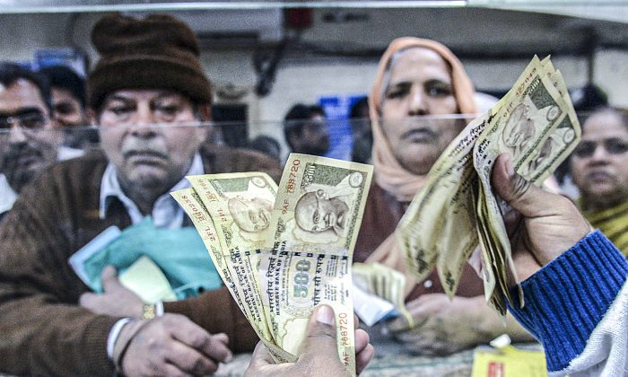An Indian bank teller counts invalidated 500-rupee notes that are being exchanged for new notes in Amritsar, India, on Nov. 19, 2016. (NARINDER NANU/AFP/Getty Images)