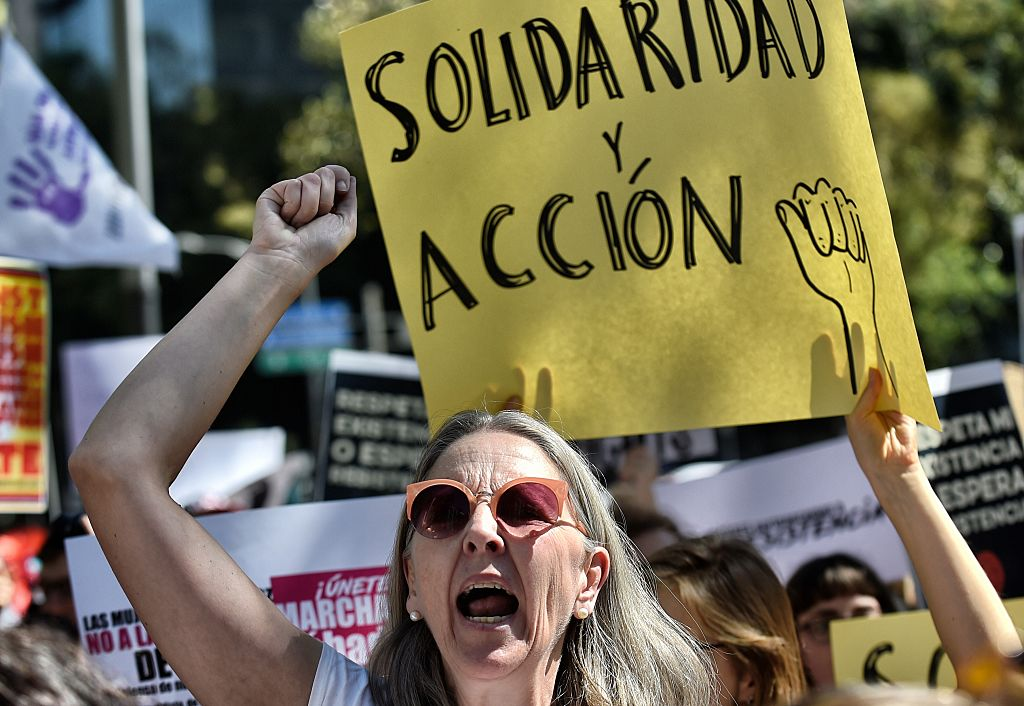 """A womna holds a sign reading """"Solidarity and action"""" during the """"Women's March"""" against new US President Donald Trump in Mexico City on Jan.21, 2017. (PEDRO PARDO/AFP/Getty Images)"""