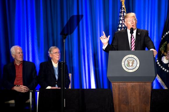 President Donald Trump speaks as Sen. John Cornyn (R-TX) (L) and Senate Majority Leader Sen. Mitch McConnell (R-KY) listen during a luncheon at the Congress of Tomorrow Republican Member Retreat in Philadelphia, Pennsylvania on Jan. 26, 2017. (Bill Clark-Pool/Getty Images)
