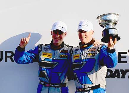 Cameron Cassels and Trent Hindman, drivers of the #12 Bodymotion Racing Porsche Cayman GT4 celebrate on the podium after winning the IMSA CTSCC BMW Endurance Challenge at Daytona Friday, Jan. 27. (Bill Kent/Epoch Times)