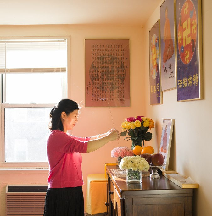 Wang Huijuan pays her respects to the founder of Falun Gong at her home in Queens, New York, on Jan. 8, 2016. With her husband and daughter, she escaped China in 2014 and was granted asylum after years of torture for practicing Falun Gong. (Samira Bouaou/Epoch Times)