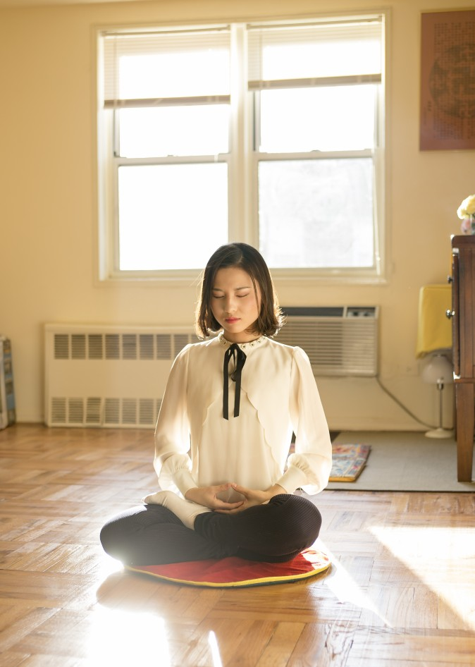 Li Fuyao demonstrates her meditation practice at her home in Queens, New York, on Jan. 8, 2016. She and her parents escaped China in 2014 and were granted asylum after years of torture for practicing Falun Gong. (Samira Bouaou/Epoch Times)