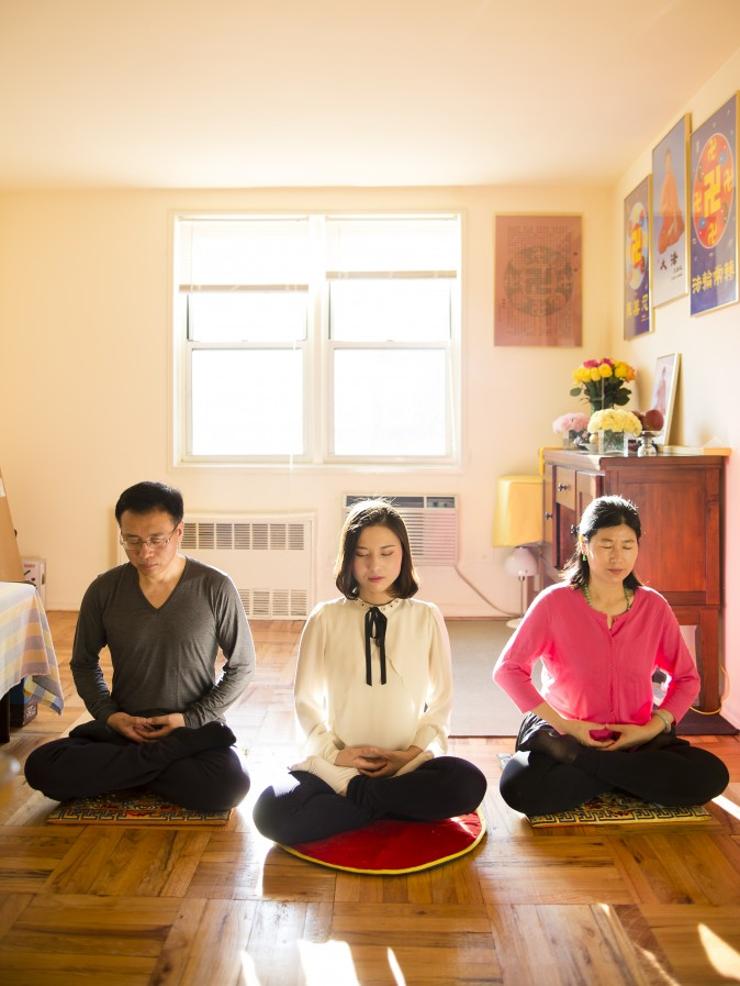 (L-R) Li Zhenjun, Li Fuyao, and Wang Huijuan demonstrate their meditation practice at their home in Queens, New York, on Jan. 8, 2016. They escaped China in 2014 and were granted asylum after years of torture for practicing Falun Gong. (Samira Bouaou/Epoch Times)