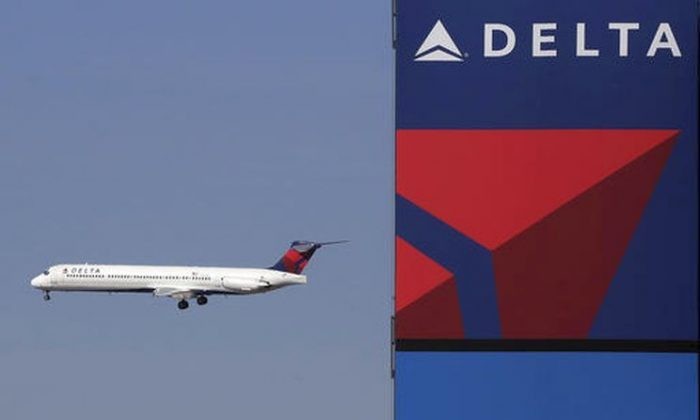 A Delta Airlines jet flies past the company's billboard at Citi Field, in New York on In this Saturday, April 6, 2013. (AP Photo/Mark Lennihan, File)