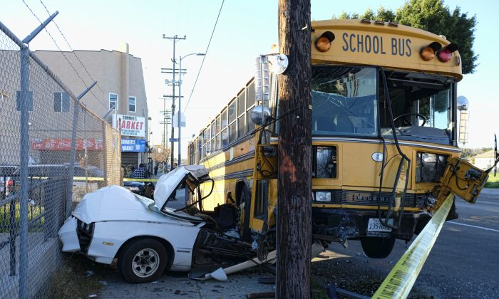 A car is wedged under a school bus that crashed in South Los Angeles on Jan. 27, 2017. (AP Photo/Richard Vogel)
