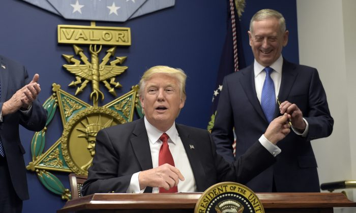 President Donald Trump (L) hands Defense Secretary James Mattis (R) a pen after he signed an executive action on rebuilding the military during an event at the Pentagon in Washington on Jan. 27, 2017. (AP Photo/Susan Walsh)