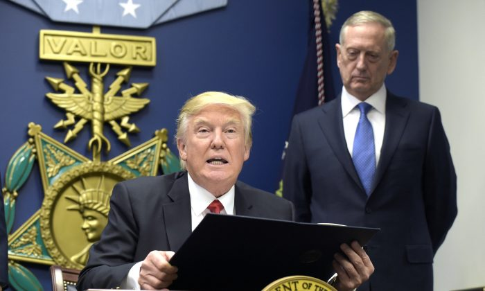 President Donald Trump, left, with Defense Secretary James Mattis, right, watching, explains the executive action on extreme vetting that he is about to sign at the Pentagon in Washington on Jan. 27, 2017. (AP Photo/Susan Walsh)