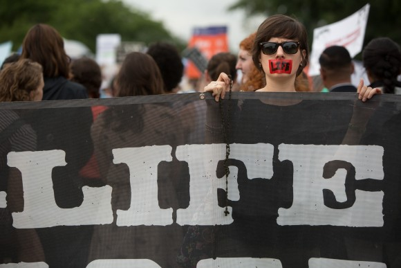 A pro-life protester holds a sign in front of the U.S. Supreme Court on a day where two important decisions on immigration and affirmative action were handed down by the court in Washington, DC, on June 23, 2016. (Allison Shelley/Getty Images)