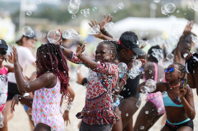 """Children play with soap bubble along the beach in Deauville, northwestern France, as part of the """"Forgotten by the Holidays"""" campaign organized by the French NGO Secours Populaire for children whose families can not afford to go on holidays on on Aug. 23. (CHARLY TRIBALLEAU/AFP/Getty Images)"""