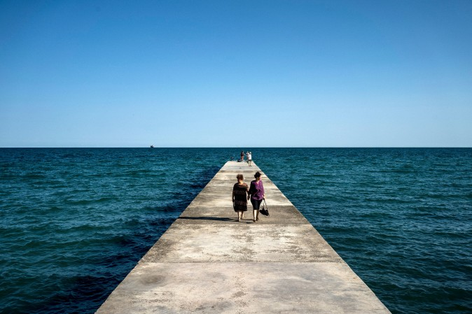 Tourists stroll on a pier in the Black Sea town of Balchik on Aug. 25. (DIMITAR DILKOFF/AFP/Getty Images)