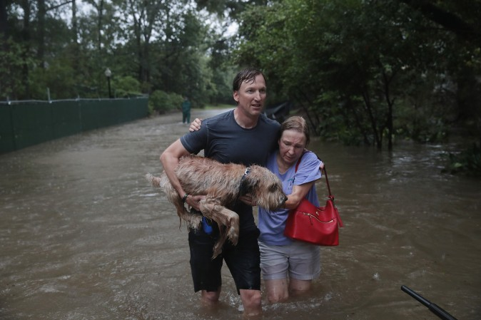 Andrew White (L) helps a neighbor down a street after rescuing her from her home in his boat in the upscale River Oaks neighborhood that was inundated with flooding from Hurricane Harvey in Houston on Aug. 27. (Scott Olson/Getty Images)