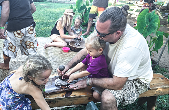 Michael Young pounds poi with his daughter Mila (L) and son Manu at the 2016 Waipa Festival in Kauai, Hawaii. (Courtesy of Michael Young)