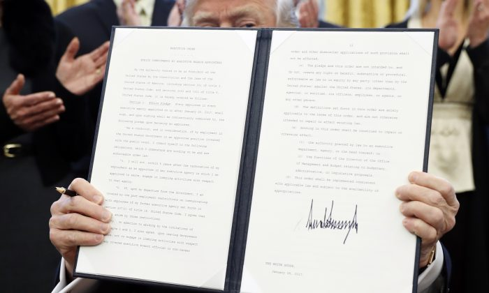 """President Donald Trump holds up a signed Executive Order in the Oval Office of the White House in Washington on Jan. 28, 2017. The document includes restrictions against lobbying for """"Every appointee in every executive agency appointed on or after January 20, 2017..."""" (AP Photo/Alex Brandon)"""