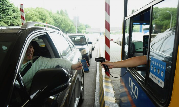 A driver uses his smartphone to pay the highway toll using Alipay, an app of Alibaba's online payment service, at a toll station on the Hangzhou-Ningbo Expressway in Hangzhou, China. (STR/AFP/Getty Images)