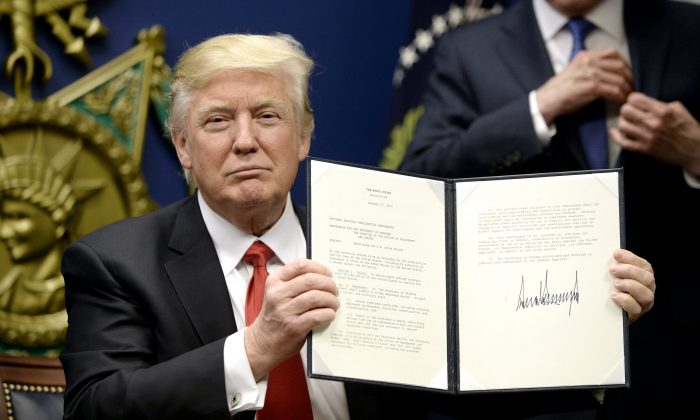 President Donald Trump signs executive orders in the Hall of Heroes at the Department of Defense in Arlington, Virginia on Jan. 27, 2017. (Olivier Douliery-Pool/Getty Images)