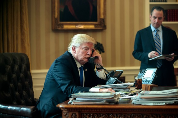 White House Chief of Staff Reince Priebus (R) looks on as President Donald Trump speaks on the phone with Russian President Vladimir Putin in the Oval Office of the White House in Washington, DC, on Jan. 28, 2017. (Drew Angerer/Getty Images)