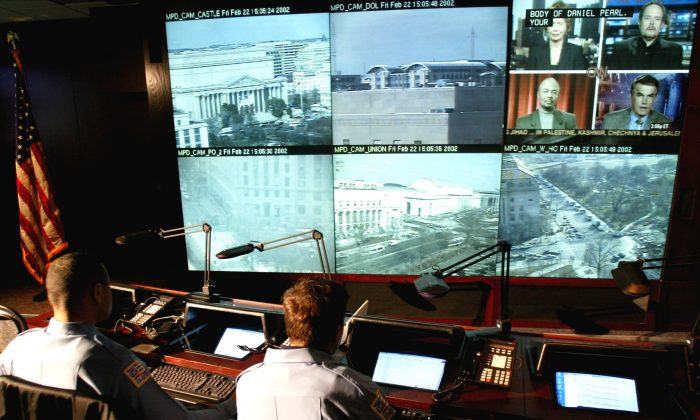 Police officers watch surveillance camera monitors in a command center at Police Headquarters in Washington, DC, in this Feb. 22, 2002 file photo. (Mark Wilson/Getty Images)