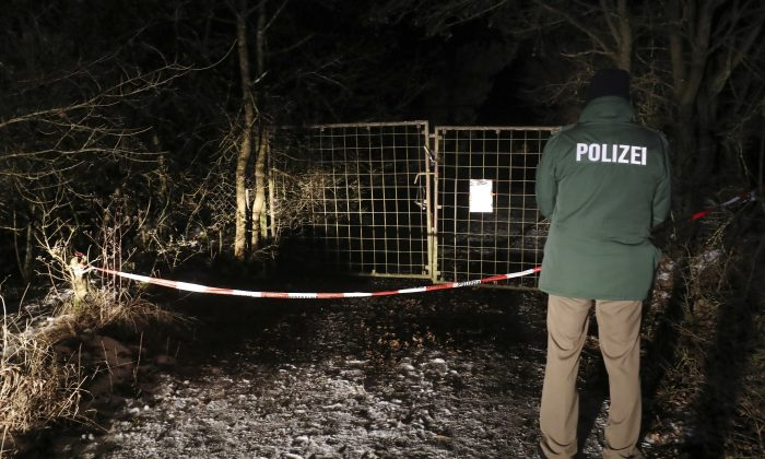 A police officer stands in front of a closed off entrance to a private ground near Arnstein, Germany Jan. 29, 2017. (Daniel Karmann/dpa via AP)