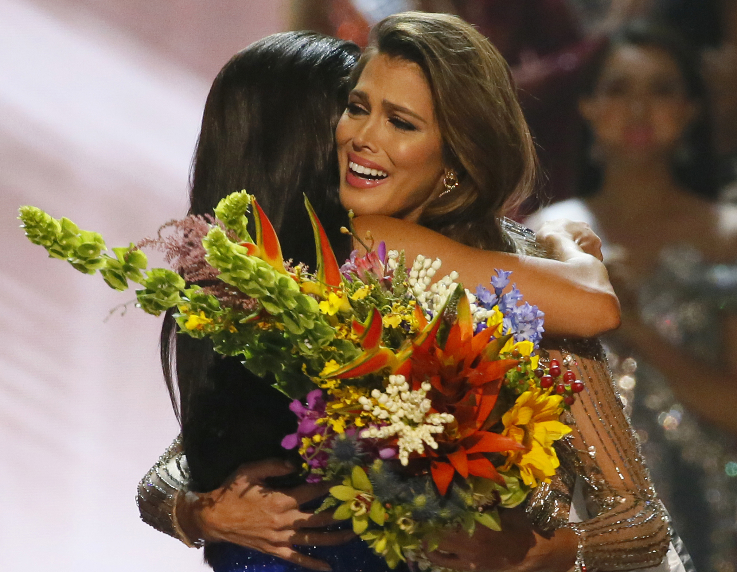 Miss Universe 2016 Iris Mittenaere (R) of France is hugged by Miss Universe 2015 Pia Wurtzbach following coronation at the Mall of Asia in suburban Pasay city, south of Manila, Philippines on Jan. 30, 2017. (AP Photo/Bullit Marquez)