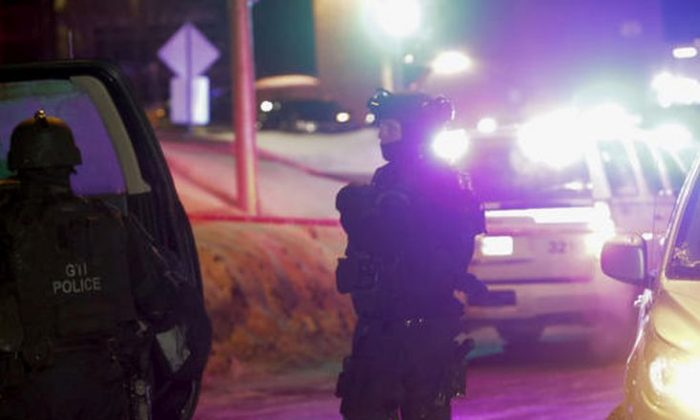 "Police survey the scene after a deadly shooting at a mosque in Quebec City, Canada, Sunday, Jan. 29, 2017. Quebec Premier Philippe Couillard termed the act ""barbaric violence"" and expressed solidarity with victims' families. (Francis Vachon/The Canadian Press via AP)"
