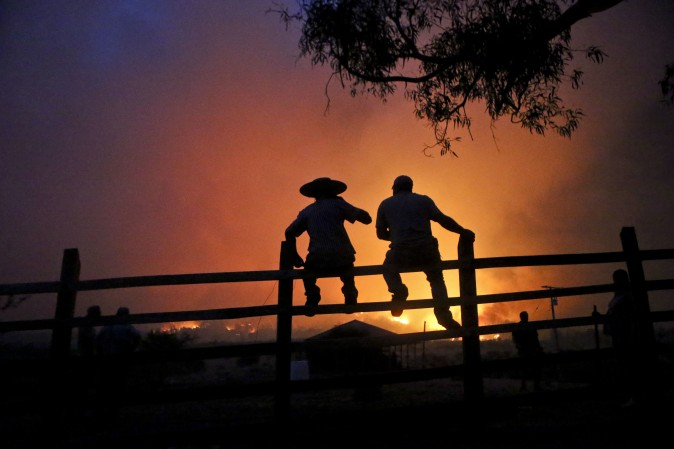 Residents watch the forest burn in Portezuelo, Chile, on Jan. 29, 2017. Chilean President Michelle Bachelet has announced that the country will continue with its various measures to deal with wild fires, one of the biggest natural disasters in the country for decades. (AP Photo/Esteban Felix)
