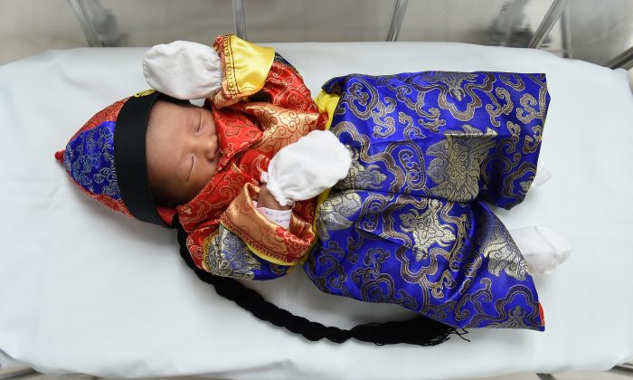 A newborn baby in a Chinese-inspired costume to mark the Year of the Rooster lays in a cot at Paolo Memorial Hospital in Bangkok on January 27, 2017. (AFP / Lillian Suwanrumpha)