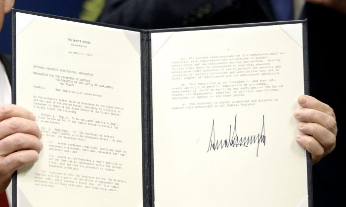 President Donald Trump signs executive orders in the Hall of Heroes at the Department of Defense in Arlington, Virginia on Jan. 27, 2017. Trump signed two orders calling for the 'great rebuilding' of the nation's military and the 'extreme vetting' of visa seekers from terror-plagued countries. (Olivier Douliery-Pool/Getty Images)