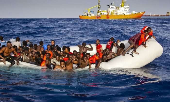 Migrants on an overcrowded boat call for help off the coast of the Italian island of Lampedusa on April 17, 2016. (Patrick Bar/SOS Mediterranee via AP)