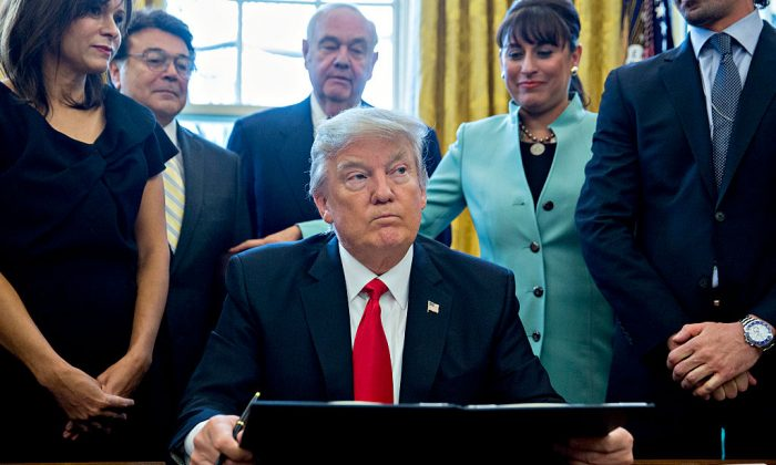 U.S. President Donald Trump pauses after signing an executive order in the Oval Office of the White House surrounded by small business leaders in Washington, DC. on Jan. 30, 2017. (Andrew Harrer - Pool/Getty Images)