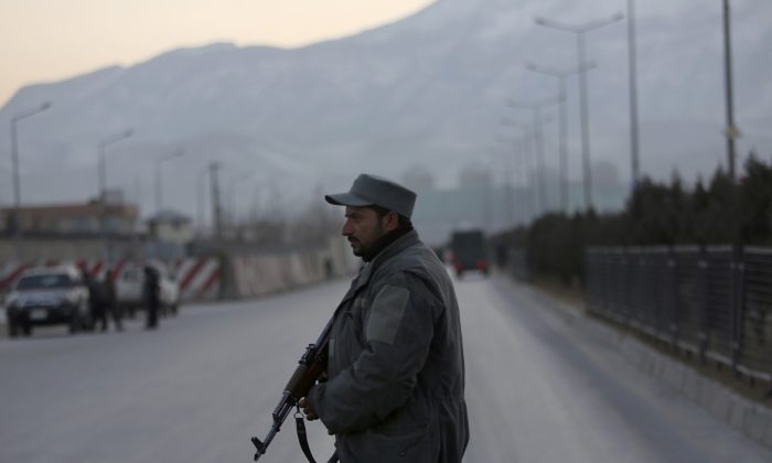 An Afghan security officer stands guard near the site of two blasts in Kabul, Afghanistan, on Jan. 10. (AP Photo/Rahmat Gul)