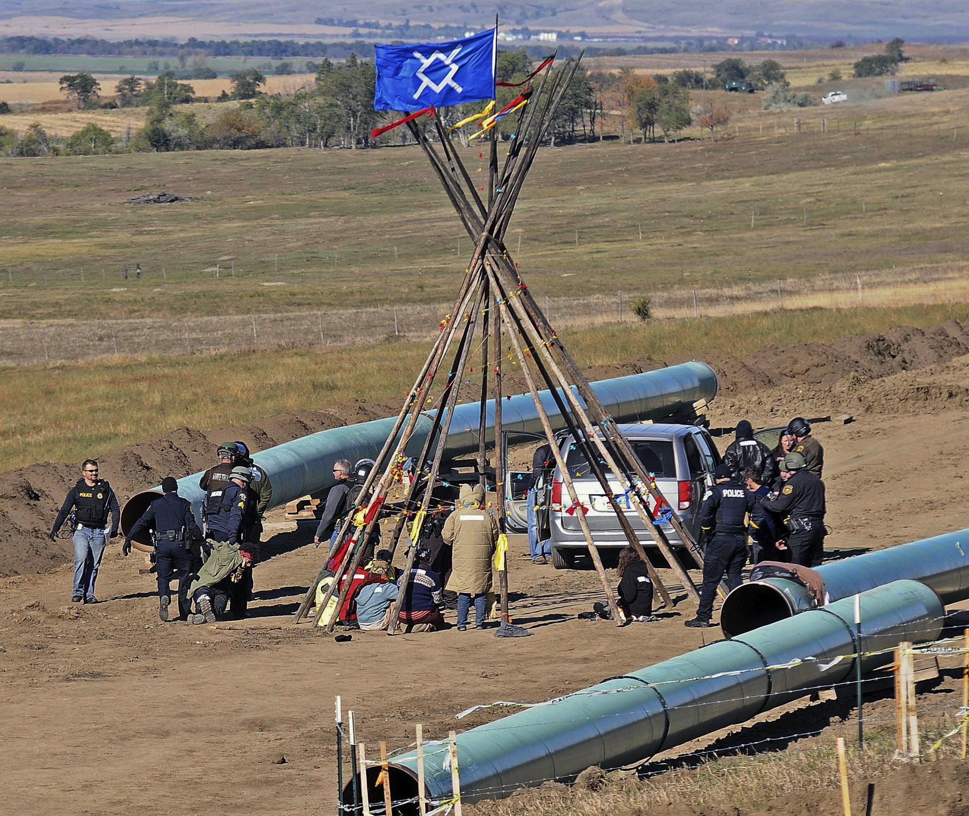 Law enforcement officers (L) drag a person from a protest against the Dakota Access Pipeline, near the town of St. Anthony in rural Morton County, N.D., on Oct. 10, 2016. (Tom Stromme/The Bismarck Tribune via AP)