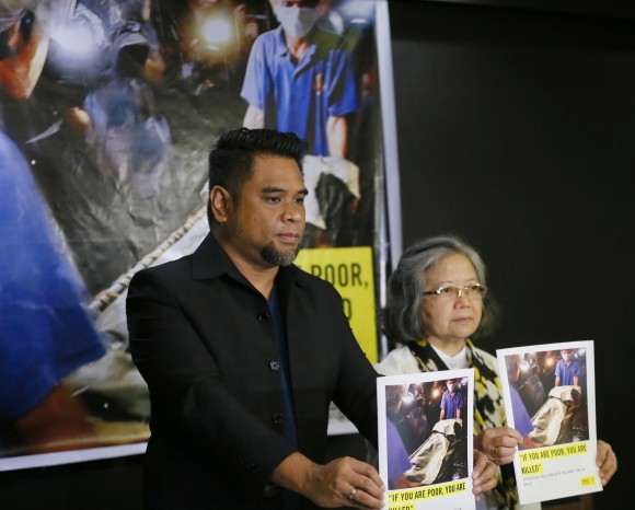 """Amnesty International campaigner Wilnor Papa, left, and Board of Trustee Sis. Maria Vida Cordero hold copies of the Amnesty's repport on extra-judicial killings in the country following a video news conference with their London counterpart Rachel Chhoa-Howard, in suburban Quezon city, northeast of Manila, Philippines Wednesday, Feb. 1, 2017. A majority of the thousands of killings of poor suspects under Philippine President Rodrigo Duterte's anti-drug crackdown appear to be """"extrajudicial executions,"""" Amnesty International said Wednesday, and may constitute crimes against humanity. (AP Photo/Bullit Marquez)"""