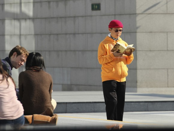 In this Dec. 2013, photo, Xiao Jianhua, a Chinese-born Canadian billionaire, reads a book outside the International Finance Centre in Hong Kong. Mystery surrounds the whereabouts of Xiao reportedly taken away from his Hong Kong hotel by mainland police, in a case that could rekindle concerns about overreach by Chinese law enforcement in the semiautonomous city. (AP Photo/Next Magazine)