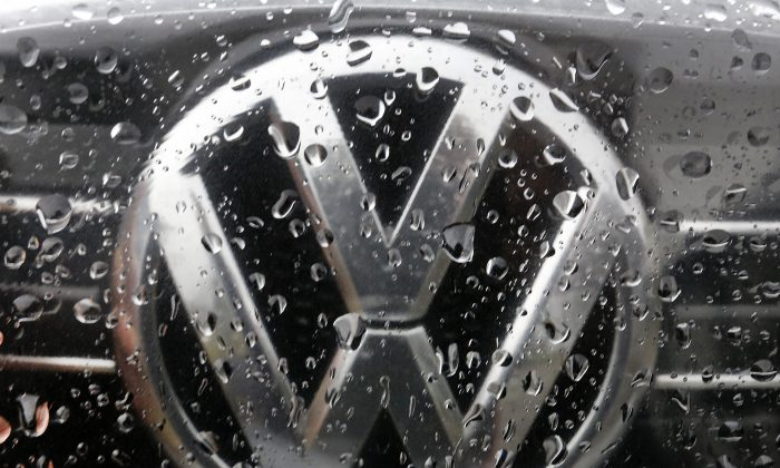 FILE - In this Nov. 18, 2016 file photo the Volkswagen logo is photographed through rain drops on a window in Frankfurt, Germany. Volkswagen has agreed to pay at least US$ 1.2 billion in buybacks and compensation to settle claims from U.S. owners of cars with larger diesel engines that the company rigged to cheat on emissions tests. The proposed settlement filed late Tuesday, Jan. 31, 2017 in U.S. District Court in San Francisco covers owners of some 75,000 Audi, Volkswagen and Porsche cars with 3.0-liter diesel engines. (AP Photo/Michael Probst)