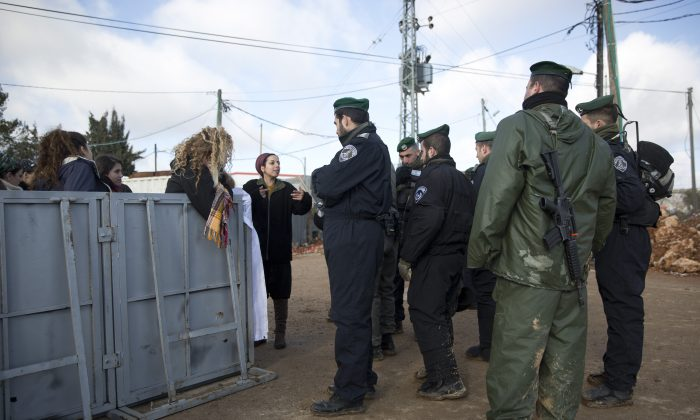 Settlers talk to Israeli police in Amona outpost, on Feb. 1, 2017. (AP Photo/Oded Balilty)