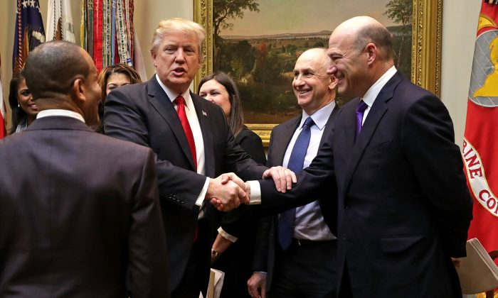 President Donald Trump (L) calls White House Director of Strategic Initiatives Chris Liddell and White House Director of the National Economic Council Gary Cohn (R) 'geniuses' as he arrive for a meeting with small business people in the Roosevelt Room at the White House in Washington on Jan. 30, 2017. (Chip Somodevilla/Getty Images)