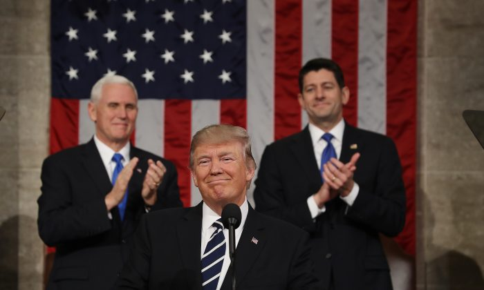 Vice President Mike Pence (L) and Speaker of the House Paul Ryan (R) applaud as U.S. President Donald J. Trump (C) arrives to deliver his first address to a joint session of the U.S. Congress in the House chamber of the U.S. Capitol in Washington on Feb. 28, 2017. (Jim Lo Scalzo - Pool/Getty Images)