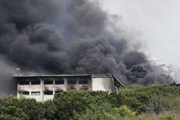 Smoke rises from a huge fire at the House Technology Industries (HTI) factory inside the Export Processing Zone Authority for more than twenty hours, in General Trias township, Cavite province south of Manila, Philippines, on Feb. 2, 2017. (AP Photo/Bullit Marquez)