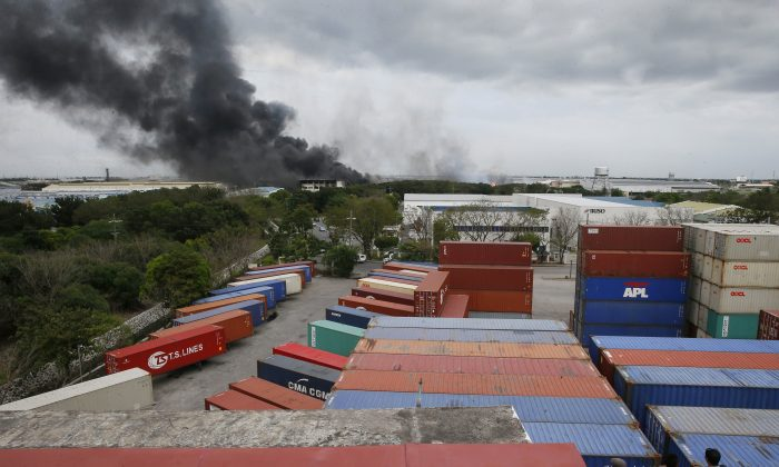 Residents watch smoke rise from a huge fire at the House Technology Industries (HTI) factory inside the Export Processing Zone Authority for more than twenty hours, in General Trias township, Cavite province south of Manila, Philippines, on Feb. 2, 2017. (AP Photo/Bullit Marquez)