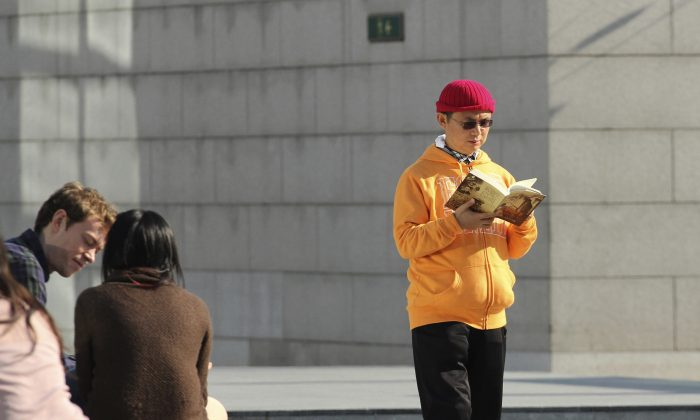 Xiao Jianhua, a Chinese-born Canadian billionaire, reads a book outside the International Finance Centre in Hong Kong in December 2013. (AP Photo/Next Magazine)