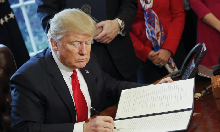 President Donald Trump signs an executive order in the Oval Office of the White House in Washington, Friday, Feb. 3, 2017. Trump signed an executive order that will direct the Treasury secretary to review the 2010 Dodd-Frank financial oversight law, which reshaped financial regulation after 2008-2009 crisis. (AP Photo/Pablo Martinez Monsivais)