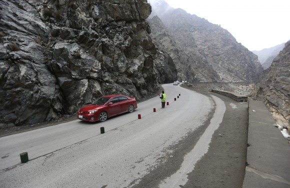 11-year-old Sedaqat signals vehicles on the Maipur Pass, along the main highway from Kabul to Pakistan, near Kabul, Afghanistan, on Jan. 5, 2017. (AP Photo/Rahmat Gul)