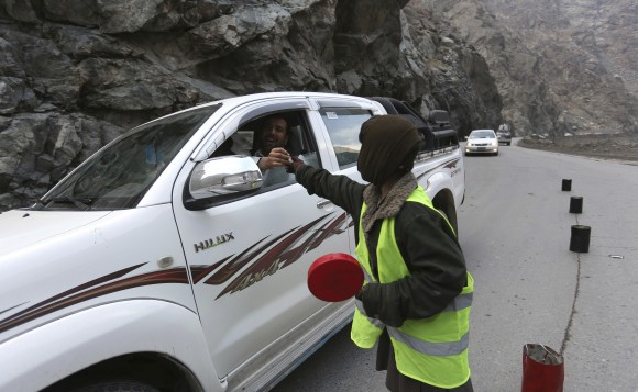 11-year-old Sedaqat receives a tip from a motorist on the Maipur Pass, along the main highway from Kabul to Pakistan, near Kabul, Afghanistan, on Jan. 5, 2017. (AP Photo/Rahmat Gul)