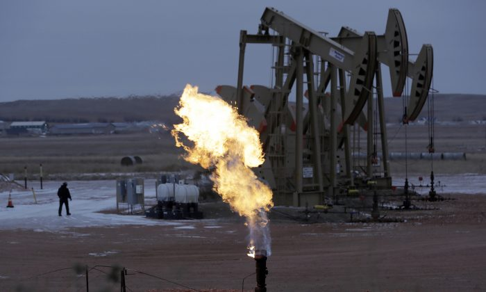 Workers tend to oil pump jacks behind a natural gas flare near Watford City, N.D., in this file photo.  (AP Photo/Eric Gay)