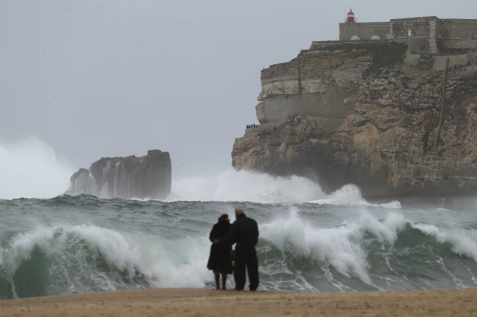 A couple watches the waves breaking in Nazare, Portugal, on Feb. 2, 2017. (AP Photo/Armando Franca)