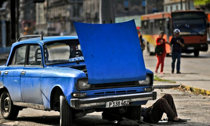A man repairs his car in Havana, on January 11, 2016. A third of the cars riding in Cuba do so with mechanical failures and on destroyed roads. (YAMIL LAGE/AFP/Getty Images)