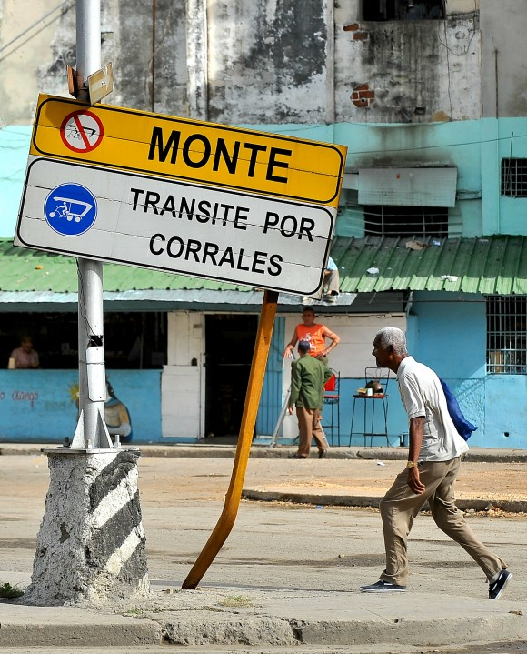 A man walks next to a traffic sign in Havana, on January 11, 2016. A third of the cars riding in Cuba do so with mechanical failures and on destroyed roads. AFP PHOTO/YAMIL LAGE / AFP / YAMIL LAGE (Photo credit should read YAMIL LAGE/AFP/Getty Images)
