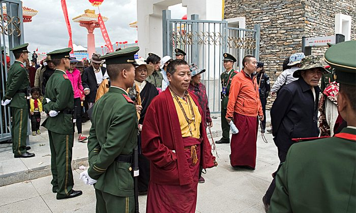 Tibetan monks walk past Chinese paramilitary police at a stadium in Qinghai Province in this file photo. (NICOLAS ASFOURI/AFP/GETTY IMAGES)