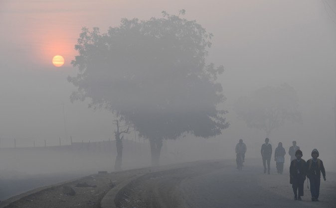 The sun rises as children walk to school on a cold foggy morning on the outskirts of New Delhi on Feb. 2, 2017. (Prakash Singh/AFP/Getty Images)