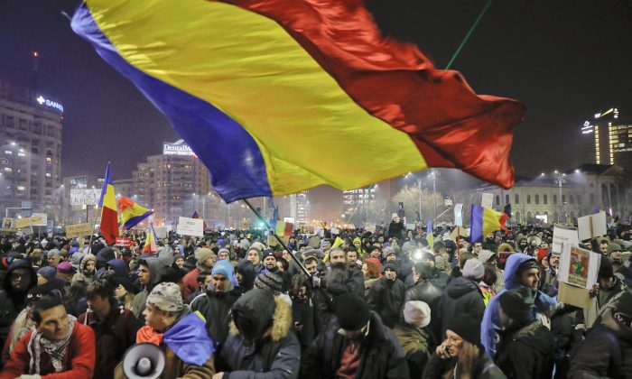 A man waves a large Romanian flag during a protest joined by tens of thousands against a government decree that dilutes what qualifies as corruption, in Bucharest, Romania, on Thursday, Feb. 2, 2017. (AP Photo/Vadim Ghirda)